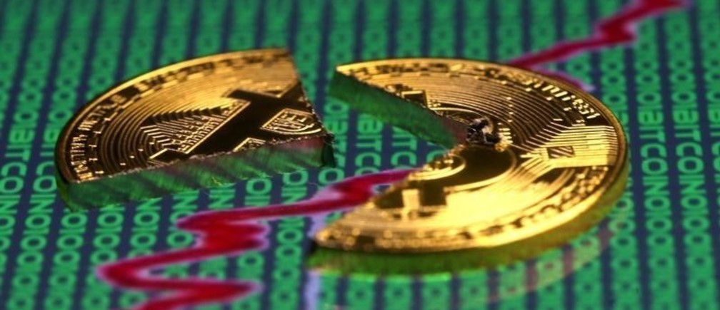 Broken representation of the Bitcoin virtual currency, placed on a monitor that displays stock graph and binary codes, are seen in this illustration picture, December 21, 2017. REUTERS/Dado Ruvic/Illustration - RC1CF88D85A0