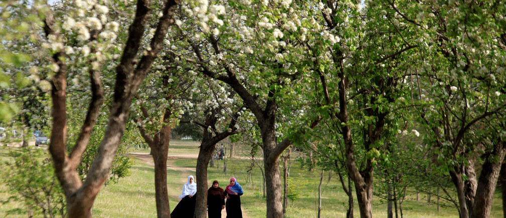 Women walk along flowering and blossoming trees along a roadside in Islamabad, Pakistan March 15, 2018. REUTERS/Faisal Mahmood - RC1D3CE6BFC0