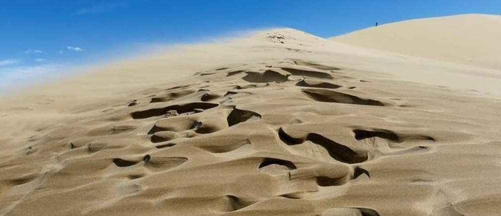 "A tourist stands at an edge of the singing sand, the 150-metre-high by three-kilometre-long dune that generates a low-pitched, organ-like rumble in dry weather, in Altyn-Emel national park in Almaty region, Kazakhstan, May 12, 2016.  REUTERS/Shamil Zhumatov       SEARCH ""SINGING SANDS"" FOR THIS STORY. SEARCH ""THE WIDER IMAGE"" FOR ALL STORIES     TPX IMAGES OF THE DAY"
