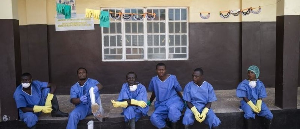 Health workers rest outside a quarantine zone at a Red Cross facility in the town of Koidu, Kono district in Eastern Sierra Leone December 19, 2014. Sierra Leone, neighbouring Guinea and Liberia are at the heart of the world's worst recorded outbreak of Ebola. Rates of infection are rising fastest in Sierra Leone, which now accounts for more than half of the 18,603 confirmed cases of the virus. REUTERS/Baz Ratner (SIERRA LEONE - Tags: HEALTH DISASTER TPX IMAGES OF THE DAY) - GM1EACJ1T7L01