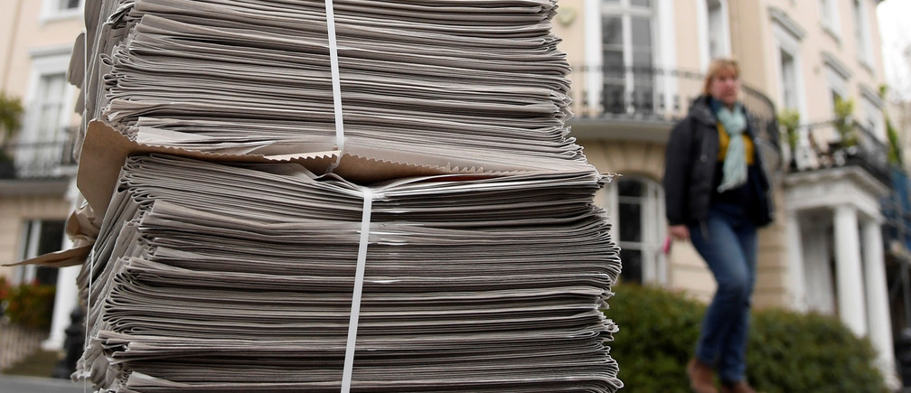 A pile of London Evening Standard newspapers are seen on a pavement awaiting delivery to homes in London, as the spread of the coronavirus disease (COVID-19) continues, London, Britain, April 1, 2020.