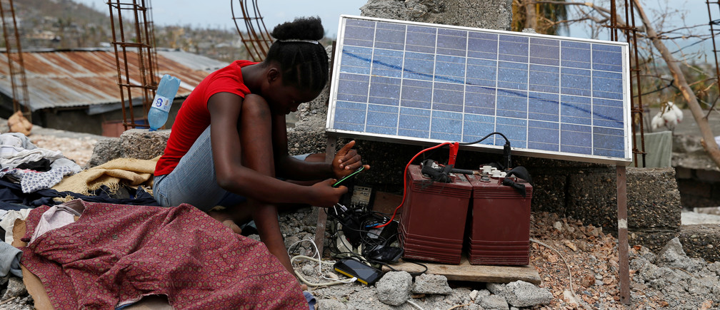 A Haitian woman charges her mobile using solar panels after Hurricane Matthew in October 2016.