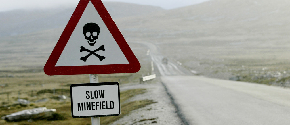 Sign placed on a side road warns locals to beware of landmines in Stanley on September 6, 2005. Most of the 150 minefields were laid around Stanley when the Argentine forces landed there on April 2, 1982 to claim the islands taken by the British in 1833. British forces defeated the Argentines 10 weeks later in a brutal war that killed 650 Argentines and 250 British. Some mines were cleared right after the conflict in a joint British-Argentine effort. Today there are 117 minefields left, 87 of them in the Stanley area where two-thirds of the islands' 2,900 people live. Picture taken September 6. To match feature Falklands-Mines. REUTERS/Enrique Marcarian - RP6DRNAVPTAA