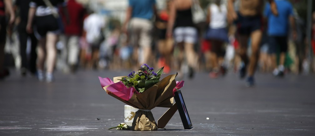 People walk near a bouquet of flowers placed in tribute to victims of the truck attack along the Promenade des Anglais on Bastille Day killing scores and injuring as many in Nice, France, July 17, 2016.
