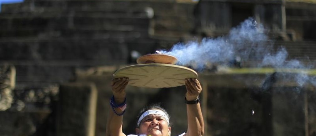 Mayte Dominuez, shaman of the town of Cuisnahuat, holds up the sacred fire during a ceremony at the Maya archeological site of Tazumal in Santa Ana, about 75 km (47 miles) away from San Salvador December 21, 2012. Mystics, hippies and tourists descended on the ruins of Maya cities to mark the close of the 13th bak'tun - a period of around 400 years - and many hoped it would lead to a better era for humanity. This week, at sunrise on Friday, December 21, an era closes in the Maya Long Count calendar, an event that has been likened by different groups to the end of days, the start of a new, more spiritual age or a good reason to hang out at old Maya temples across Mexico and Central America.  REUTERS/Ulises Rodriguez (EL SALVADOR - Tags: SOCIETY) - GM1E8CM0E4I01