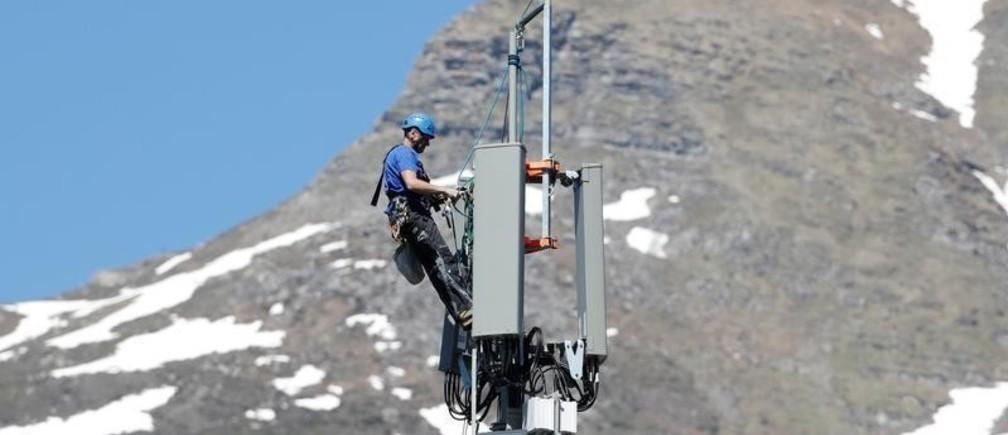 A technician is roped up as he installs 5G antennas of Swiss telecom operator Swisscom on a mast in the mountain resort of Lenzerheide, Switzerland June 13, 2019. REUTERS/Arnd Wiegmann - RC167C8B2F40