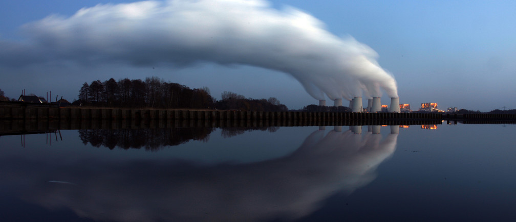 Steam billowing from the cooling towers of Vattenfall's Jaenschwalde brown coal power station is reflected in the water of a lake near Cottbus, eastern Germany December 2, 2009.