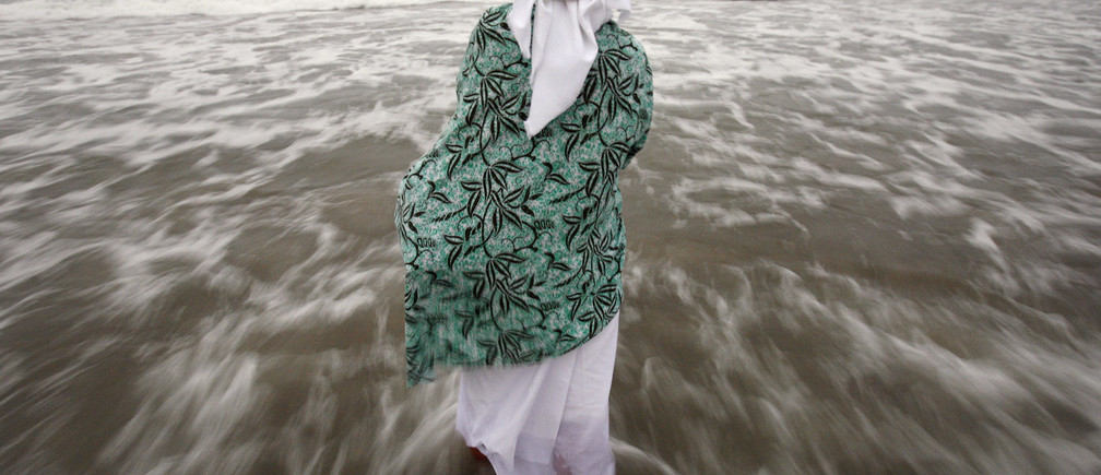A female parishioner of St. Paul Community Baptist Church stands in the Atlantic Ocean during a Maafa Commemoration in New York September 22, 2007. The Maafa Commemoration honors the millions of Africans lost in the Trans-Atlantic Slave Trade and Middle Passage.  REUTERS/Shannon Stapleton (UNITED STATES) - GM1DWFDJWZAA