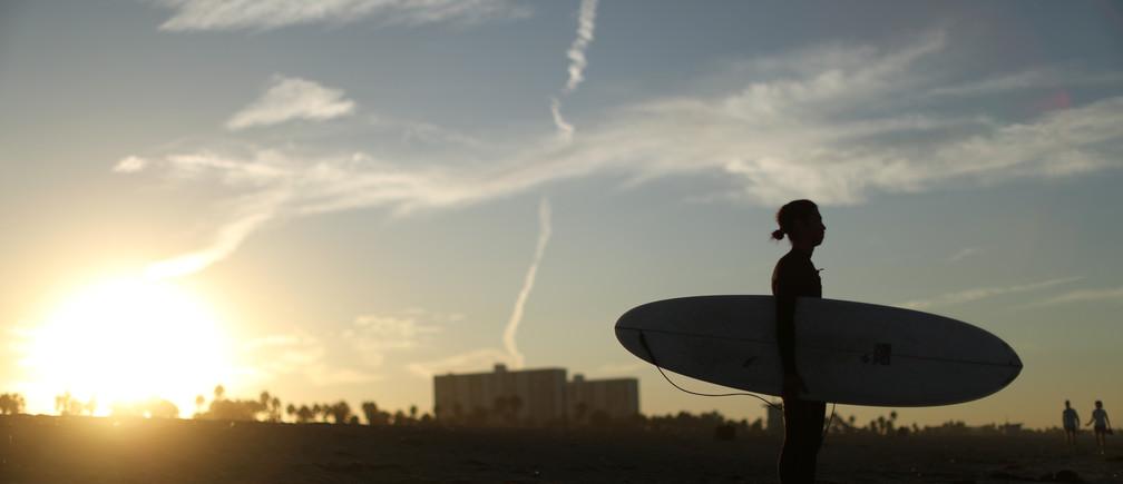 A surfer walks into the Pacific Ocean near the Santa Monica Pier as the sun rises in Santa Monica, California, U.S. October 16, 2017. REUTERS/Lucy Nicholson - RC113E405FE0