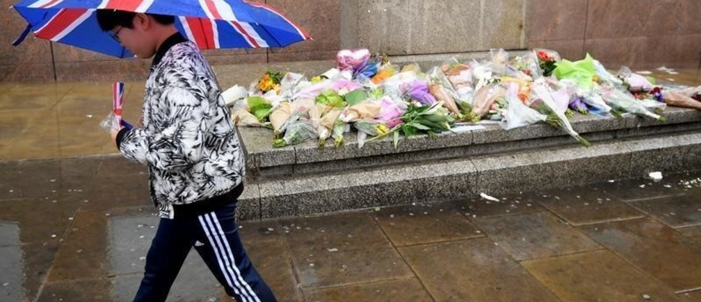 A pedestrian carrying an umbrella walks past floral tributes to the victims of the recent attack at London Bridge and Borough Market, in central London, Britain June 6, 2017.  REUTERS/Toby Melville - RTX39894