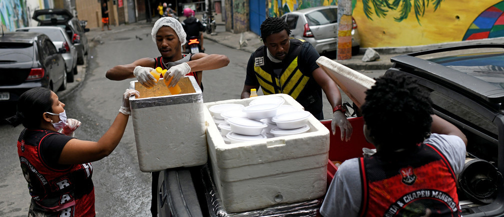 A group of residents of the marginal neighborhood of Chapeu Mangueira, carry boxes of food to give to homeless people in the Copacabana neighborhood during the outbreak of coronavirus disease (COVID-19), in Rio de Janeiro, Brazil, on April 11 2020.