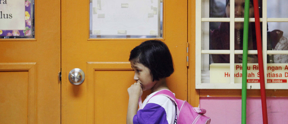 Preschooler Nuranisya Alihasdi, 6, refuses to join her classmates as her mother quietly watches her during the first day of school in Putrajaya outside Kuala Lumpur January 4, 2012. REUTERS/Bazuki Muhammad (MALAYSIA - Tags: EDUCATION SOCIETY) - GM1E81411W001