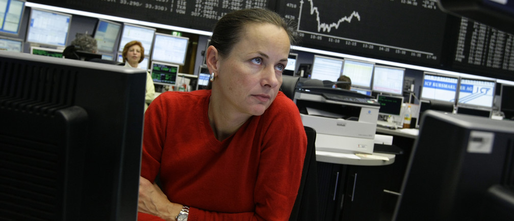 A trader watches her screens in front of the main board showing the DAX curve at the Frankfurt stock exchange December 17, 2008. European shares fell in early trade on Wednesday as investors shrugged off a Federal Reserve rate cut and focused instead on worries about more banking sector losses.      REUTERS/Alex Grimm (GERMANY) - RTR22NM8