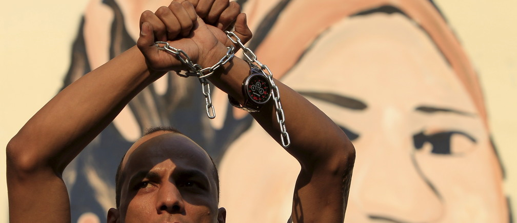 A protester holds up his hands, which are chained together, as journalists and members of the April 6 movement protest against the restriction of press freedom and demand the release of detained journalists in front of the Press Syndicate in Cairo June 10, 2015. Egyptian security forces have arrested dozens of activists ahead of a general strike planned for Thursday, activists and security sources say, part of what the activists describe as an unrelenting crackdown on dissent. REUTERS/Mohamed Abd El Ghany - RTX1FZRF