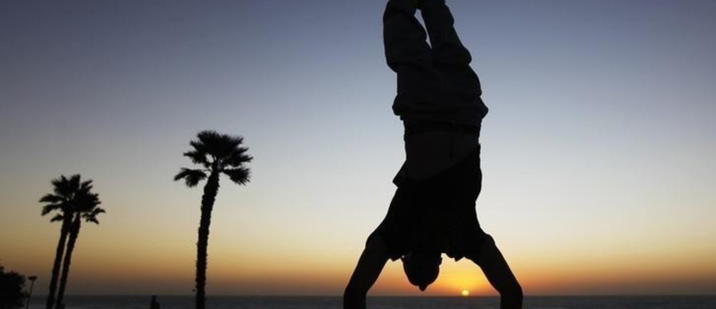 A youth practices parkour, also known as free-running, as he does a handstand at the seaside in the city of Netanya December 23, 2011. Parkour is a method of movement, originally from France, whose practitioners use techniques of vaulting, rolling, running, climbing and jumping to leap over or move around obstacles.