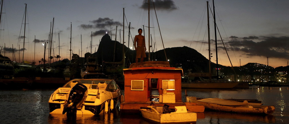 Naval carpenter Alexandro de Oliveira, 41, stands atop his boat house in the waters of the Guanabara Bay in Rio de Janeiro Brazil, April 5, 2016.