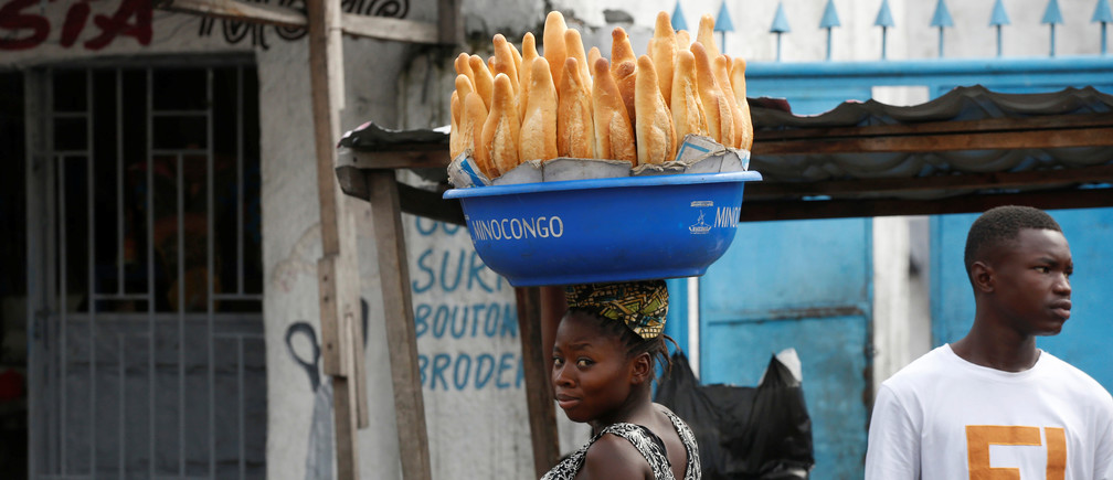 A woman carries bread on her head near the Saint Benoit church in Kinshasa, Democratic Republic of Congo, December 24, 2018. REUTERS/Baz Ratner - RC1A72002FF0