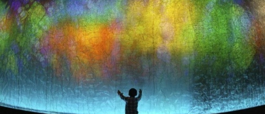 A boy touches a 45-metre (148-feet) long wall lighted by colour rays at an exhibition hall in Wuhan, central China's Hubei province May 1, 2007. Picture taken May 1, 2007. REUTERS/China Daily (CHINA) CHINA OUT