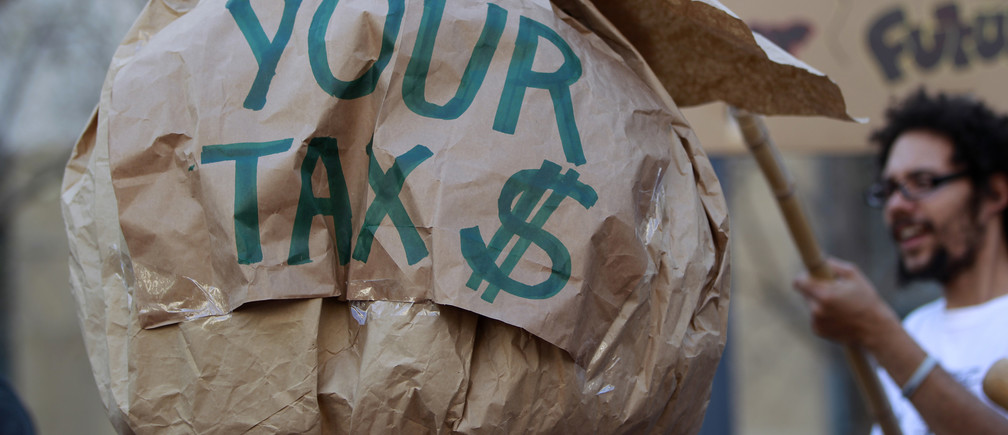 A demonstrator holds a paper-mache during a tax day protest outside Ronald V. Dellums Federal Building in Oakland, California April 17, 2012. REUTERS/Stephen Lam (UNITED STATES - Tags: POLITICS CIVIL UNREST BUSINESS) - RTR30VE5