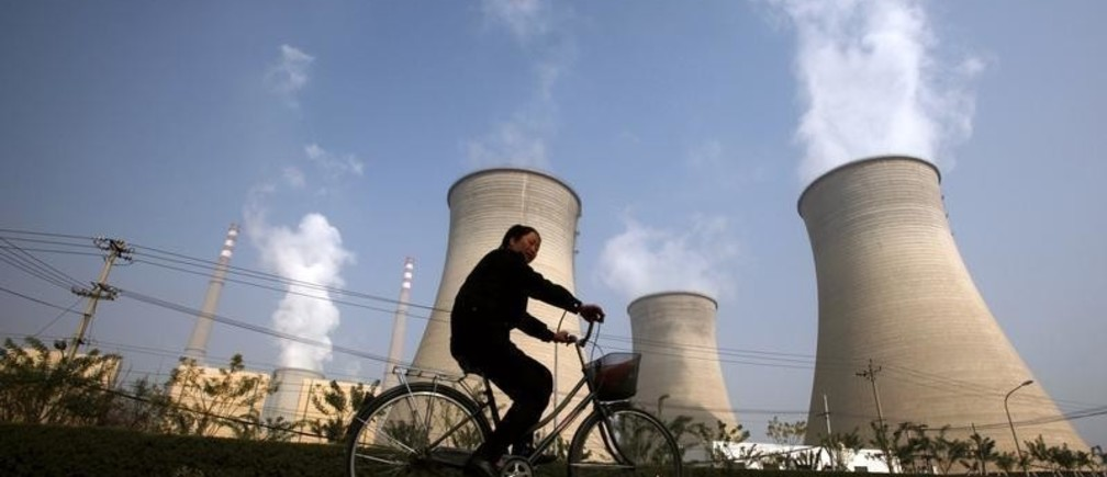 A woman rides her bicycle past the chimneys of a power station located on the outskirts of Beijing October 29, 2009. China is on track to build its first commercial-scale power plant that can capture and store emissions, but experts say it must speed up research on where and how to sequester carbon. China is the world's biggest emitter of the greenhouse gasses that cause global warming and is under increasing pressure to agree to curb output. But coal is China's most plentiful domestic source of energy, and the government hopes for decades of rapid economic expansion to lift millions more from poverty, so capturing and storing carbon dioxide is likely to be crucial to any reduction.      REUTERS/David Gray       (CHINA ENVIRONMENT POLITICS) - GM1E5AT114P01