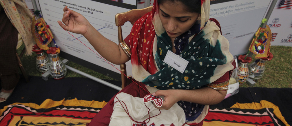 A woman works on embroidery at a stall during a visit by U.S. Agency for International Development (USAID) Administrator Rajiv Shah (unseen) in an occasion to highlight the work of female micro entrepreneurs in Karachi April 12, 2012. South Aisan women, and especially Pakistani women from rural area, are part of a rich local traditional of making beautifully embroidered handicrafts. These products could become a source of income for the women artisans and their families, USAID said in their press release. REUTERS/Akhtar Soomro   (PAKISTAN - Tags: POLITICS BUSINESS EMPLOYMENT) - GM1E84C1P4U02
