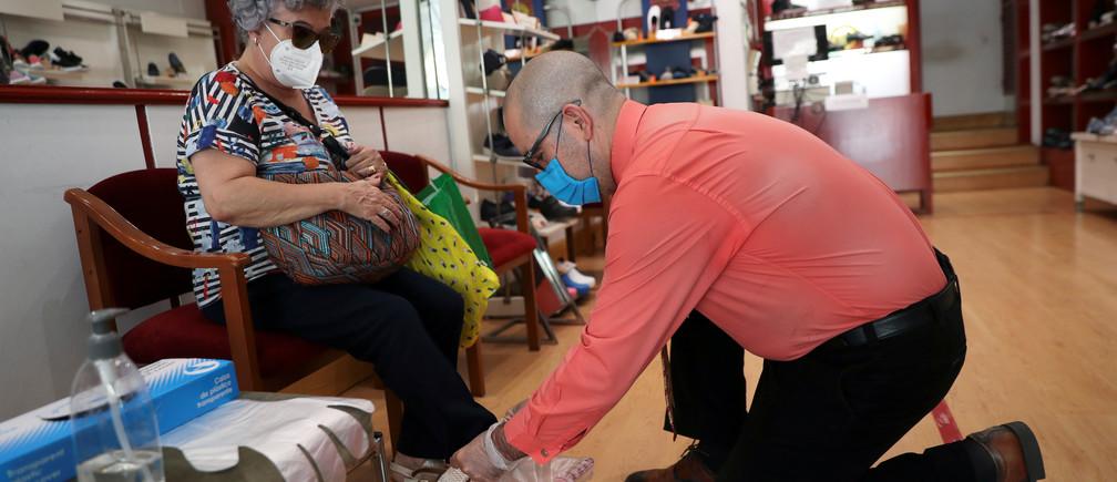 Una clienta que lleva una máscara facial protectora es asistida por la dueña mientras se prueba un par de zapatos en una zapatería, en medio del brote de la enfermedad coronavirus (COVID-19), en Madrid, España, el 19 de mayo de 2020.