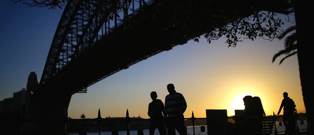 Pedestrians walk underneath the Sydney Harbour Bridge at sunset on a spring day in central Sydney, Australia, November 8, 2017.