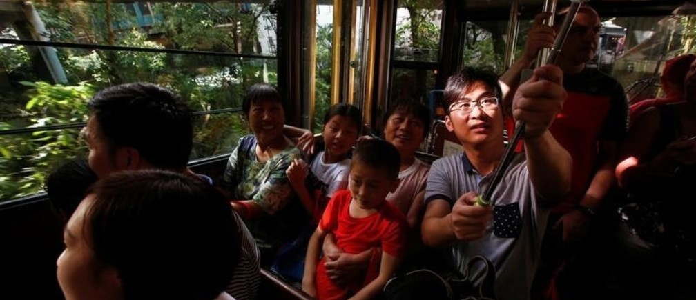 A mainland Chinese tourist takes a selfie inside a Peak Tram in Hong Kong, China August 4, 2017.    REUTERS/Bobby Yip - RC13BD7D0BD0