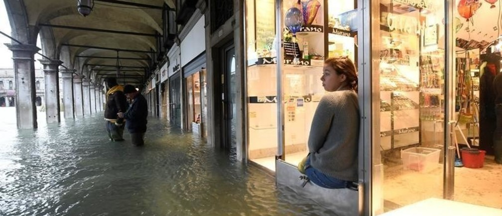 A woman looks on from a shop at the flooded St. Mark's Square, as high tide reaches peak, in Venice, Italy November 15, 2019. REUTERS/Flavio Lo Scalzo - RC2LBD9MRJ9M