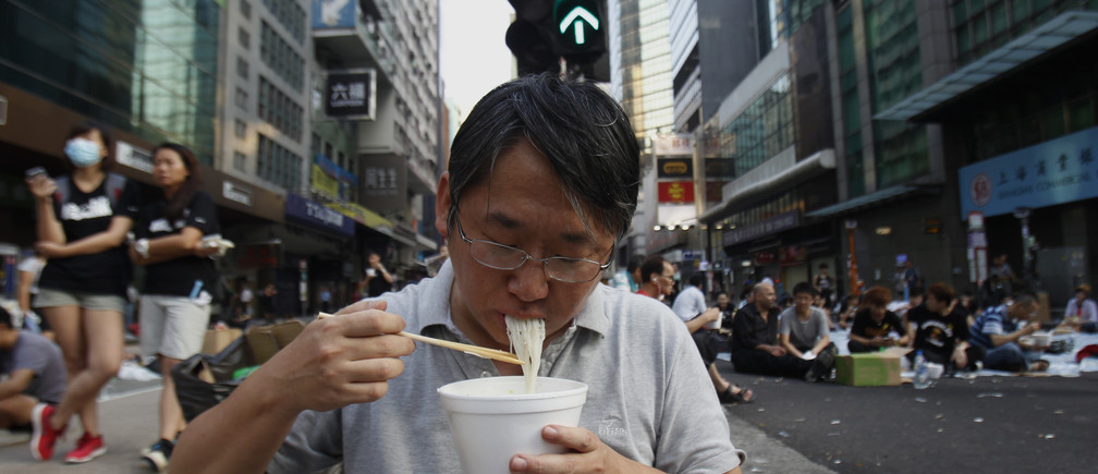 A protester eats noodles in the middle of a main road occupied by protesters, at Mongkok shopping district in Hong Kong September 30, 2014. Tens of thousands of pro-democracy protesters extended a blockade of Hong Kong streets on Tuesday, stockpiling supplies and erecting makeshift barricades ahead of what some fear may be a push by police to clear the roads before Chinese National Day.      REUTERS/Liau Chung-ren  (CHINA - Tags: POLITICS CIVIL UNREST) - RTR48B5L