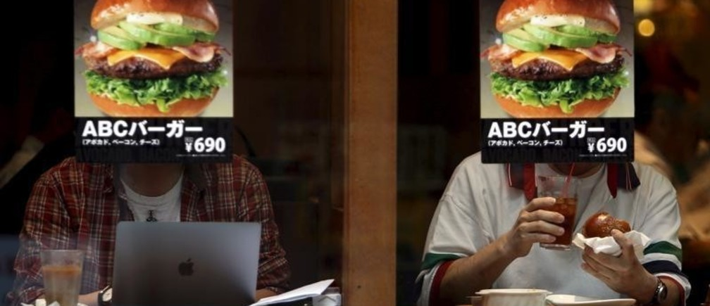 Customers sitting inside a fast food shop are seen behind its hamburger advertisement poster on a window at the Tokyo's Akihabara shopping district, Japan, May 19, 2015. Japan's economy grew at a 2.4 percent annualized rate in the January-March period, expanding for a second straight quarter on a pick-up in capital spending, the government said on Wednesday. Picture taken May 19, 2015. REUTERS/Yuya Shino - GF10000100369