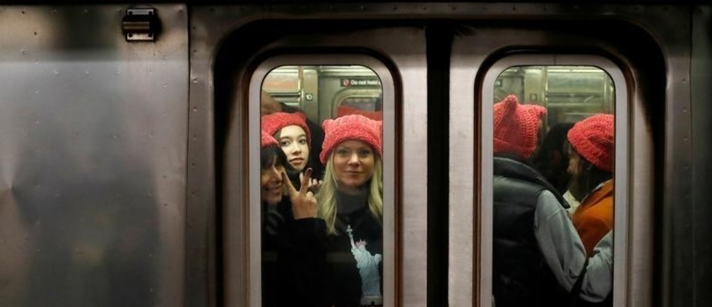 "A group of people wearing ""pussyhats"" ride the subway at 42nd Street as they head toward the Women's March in Manhattan, New York City, New York, U.S., January 20, 2018. REUTERS/Andrew Kelly     TPX IMAGES OF THE DAY - RC157BC958D0"