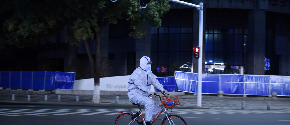 A man in a protective suit rides a shared bicycle at an intersection in Wuhan, the epicentre of the novel coronavirus outbreak, Hubei province, China March 4, 2020. REUTERS/Stringer  CHINA OUT - RC22DF9GAY33