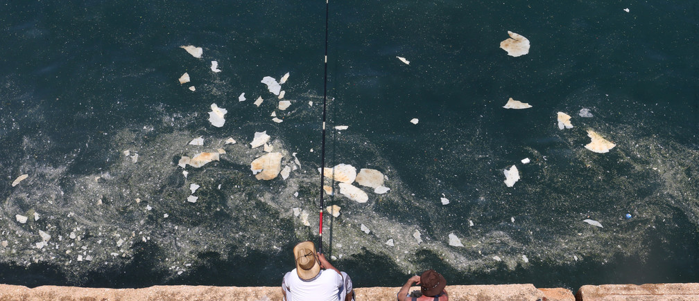 A fisherman dangles his line to catch fish in polluted water off Beirut's seaside Corniche, Lebanon June 23, 2019. REUTERS/Mohamed Azakir - RC14D8253860