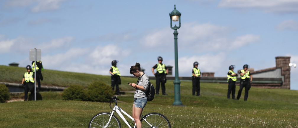 A cyclist checks her phone as police stand guard on the Plains of Abraham during a march at the G7 Summit in Quebec City, Quebec, Canada, June 8, 2018. REUTERS/Mathieu Belanger - HP1EE681K0J50