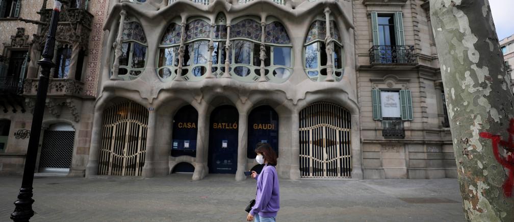 Una mujer usa una máscara facial protectora mientras pasa por delante de una Casa Batlló vacía, en medio de la preocupación por el brote de coronavirus en España, en Barcelona, España, el 15 de marzo de 2020.