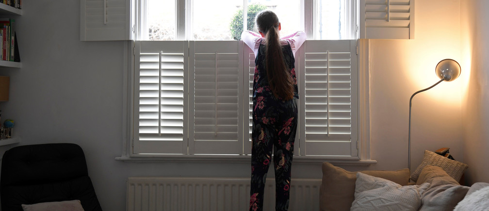 Nine-year-old Eve looks out of the front window at home, as the number of coronavirus disease (COVID-19) cases grow around the world, in London, Britain, March 17, 2020. REUTERS/Toby Melville - women men female male girls boys teenagers teens development gender gap parity equality diversity progress change feminine masculine woman man sex biology roles dynamic balance bias androgynous Coronavirus china virus health healthcare who world health organization disease deaths pandemic epidemic worries concerns Health virus contagious contagion viruses diseases disease lab laboratory doctor health dr nurse medical medicine drugs vaccines vaccinations inoculations technology testing test medicinal biotechnology biotech biology chemistry physics microscope research influenza flu cold common cold bug risk symptomes respiratory china iran italy europe asia america south america north washing hands wash hands coughs sneezes spread spreading precaution precautions health warning covid 19 cov SARS 2019ncov wuhan sarscow wuhanpneumonia  pneumonia outbreak patients unhealthy fatality mortality elderly old elder age serious death deathly deadly