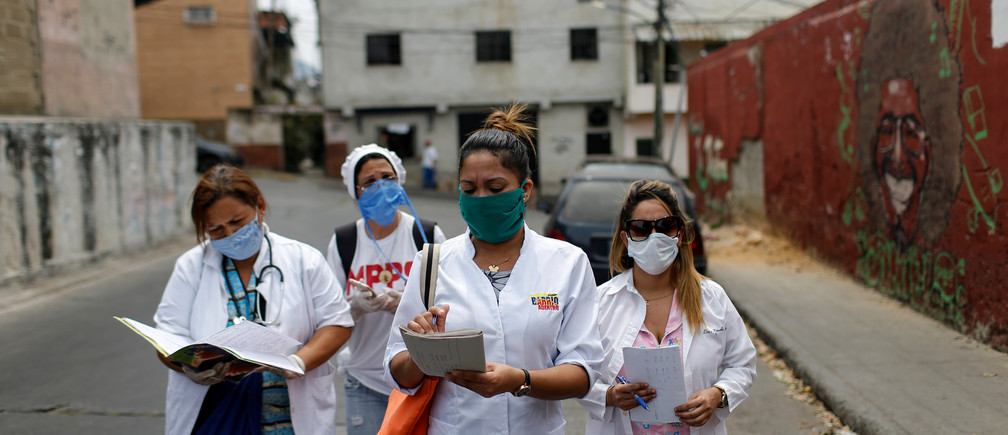A team consisting of Cuban and Venezuelan healthcare workers walk during an inspection round at the slum of Lidice during the nationwide quarantine due to the coronavirus disease (COVID-19) outbreak in Caracas, Venezuela April 9, 2020.
