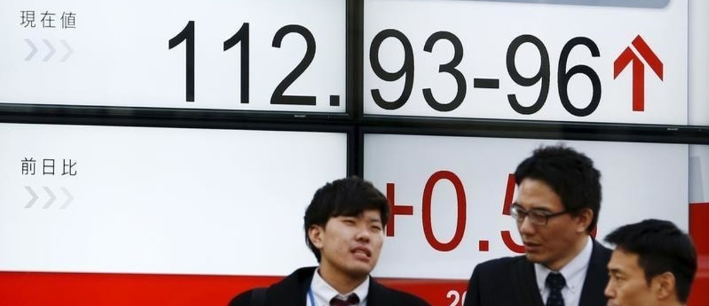 Men stand in front of a screen displaying the Dollar to Yen exchange rate in Tokyo, Japan. REUTERS/Thomas Peter