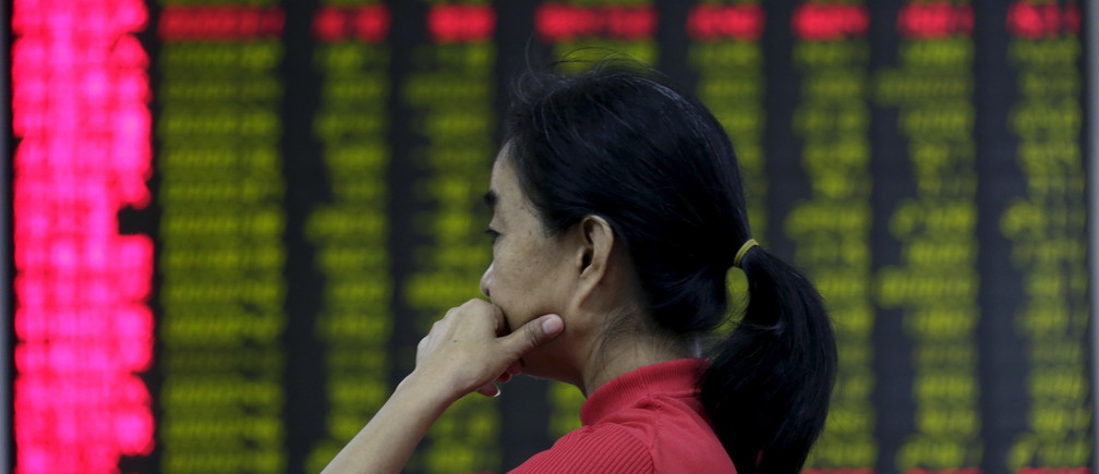 An investor looks at an electronic board showing stock information at a brokerage house in Beijing, August 26, 2015. Asian shares struggled on Wednesday as investors feared fresh rate cuts in China would not be enough to stabilise its slowing economy or halt a stock collapse that is wreaking havoc in global markets. REUTERS/Jason Lee  - GF10000182914
