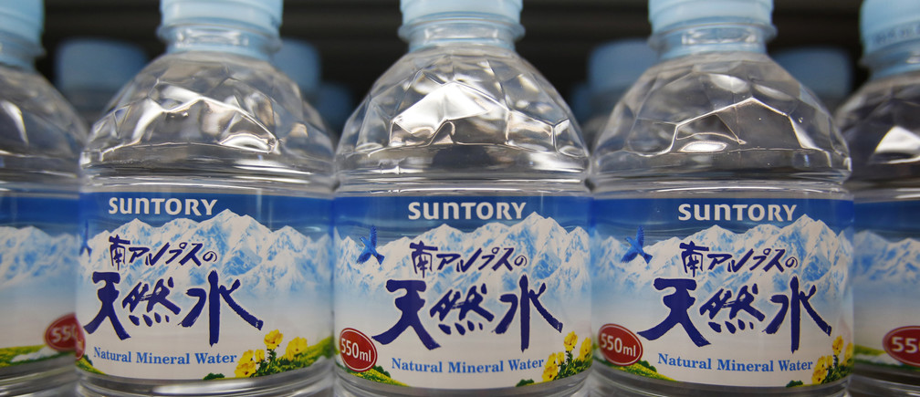 Suntory logos are seen on the labels of Suntory Beverage & Food Ltd.'s plastic bottled water displayed at a store in Tokyo February 17, 2014. The head of Suntory Holdings Ltd said on Monday the $13.6 billion takeover of U.S. whiskey maker Beam Inc would help the Japanese spirits maker expand in emerging markets Brazil, Russia, India and China.