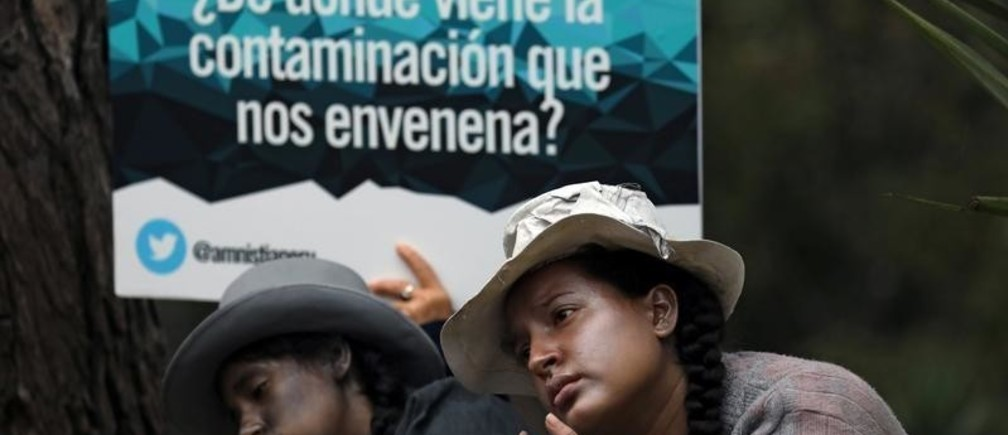 """Supporters of communities affected by toxic metals perform during a protest in front of the Health Ministry in Lima, Peru July18, 2018.  The sign reads: """"Where does the pollution that poisons us come from?"""" REUTERS/Mariana Bazo - RC1A87003460"""