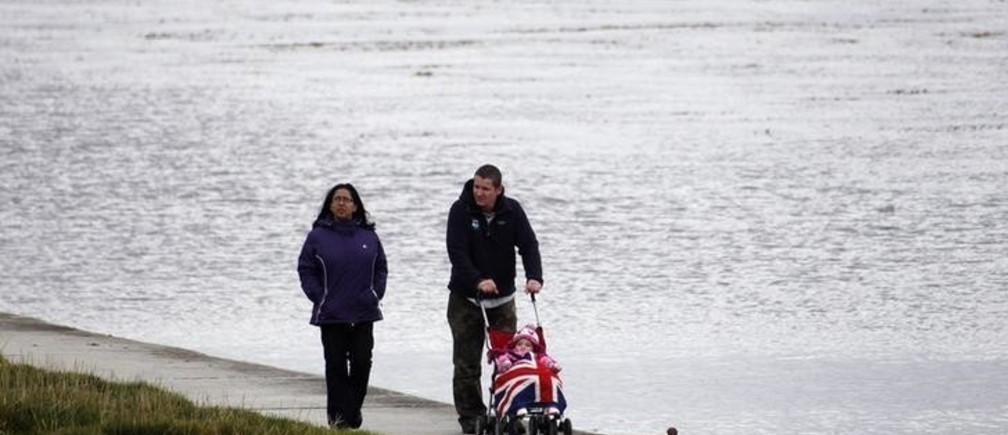 A couple walks by the shore with a pram covered with the Union Jack in Stanley March 10, 2013. REUTERS/Marcos Brindicci (FALKLAND ISLANDS - Tags: POLITICS SOCIETY)