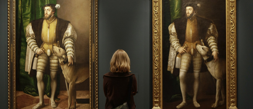 "A woman looks at paintings titled ""Carlos V con un perro"" by Austrian artist Jacob Seisenegger during the press presentation of the ""The Renaissance Portrait"" exhibition at Madrid's El Prado museum May 30, 2008. REUTERS/Juan Medina (SPAIN) - GM1E45U1QQ101"