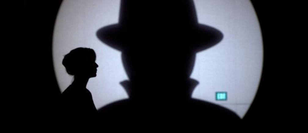 Speaker liaison Genevieve Netter is silhouetted against a Black Hat logo during the Black Hat USA 2014 hacker conference at the Mandalay Bay Convention Center in Las Vegas, Nevada August 6, 2014. REUTERS/Steve Marcus (UNITED STATES - Tags: SCIENCE TECHNOLOGY TPX IMAGES OF THE DAY) - GM1EA87044Y01