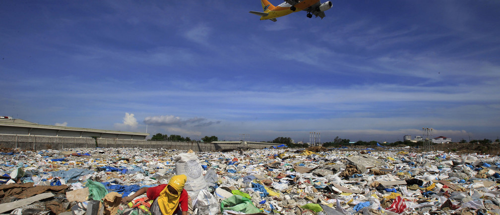 "An aircraft flies overhead as a person rummages for recyclables at a garbage dumpsite in Paranaque city, metro Manila June 8, 2014. The United Nations declared ""Small Islands and Climate Change"" the theme of 2014 World Environment Day, with the year's official 2014 slogan being ""Raise your voice, not the sea level"".          REUTERS/Romeo Ranoco (PHILIPPINES - Tags: SOCIETY ENVIRONMENT TRANSPORT TPX IMAGES OF THE DAY) - GM1EA68120W01"