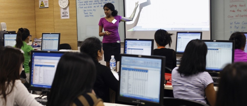 Foreign domestic workers attend a class on Microsoft Excel software, at Aidha micro business school in Singapore October 20, 2013. When she was eight, Lisa Padua lost everything after her father died, forcing her to leave school in her mid-teens to work as a maid in Qatar and then in Singapore. Twenty one years later, she still works in Singapore as a domestic helper but now owns three businesses and earns enough to send six nephews and nieces to college in the Philippines. Padua says she owes her success to Aidha, a micro school in Singapore that trains women like her in wealth and business management so they can build a better future back home in the Philippines, Indonesia and Myanmar. Picture taken October 20, 2013. To match SINGAPORE-MAIDS/ENTREPRENEURS REUTERS/Edgar Su (SINGAPORE - Tags: BUSINESS EMPLOYMENT EDUCATION SOCIETY) - RTX14J8J