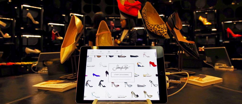 A tablet displays the Shoes of Prey website as Carmen Dang, a design consultant, stands next to designs being showcased in a large department store in central Sydney, Australia, October 1, 2015.