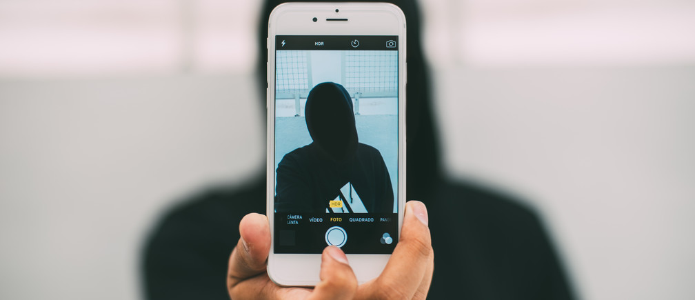 A person in a hoodie takes a selfie with a smartphone