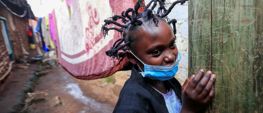"Martha Apisa, 12, poses for a photograph outside their house after plaiting with the ""coronavirus"" hairstyle, designed to emulate the prickly appearance of the virus under a microscope, as a fashion statement against the spread of the coronavirus disease (COVID-19), at Mama Brayo Beauty Salon within Kambi-Muru village of Kibera slums in Nairobi, Kenya April 29, 2020. Picture taken April 29, 2020. REUTERS/Thomas Mukoya - RC2YEG99VQE8"